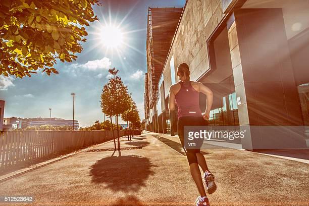 背面の眺め若い女性ジョギング街の