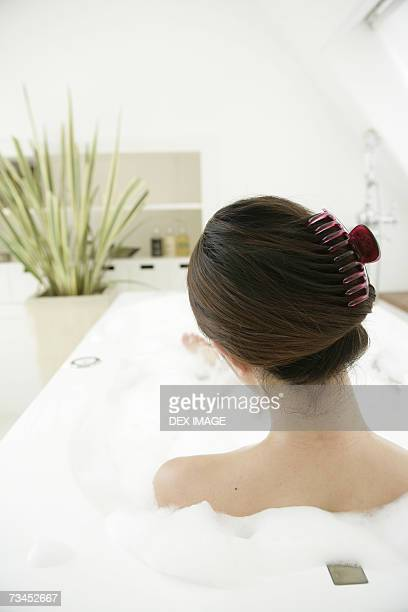 Rear view of a young woman relaxing in a bubble bath