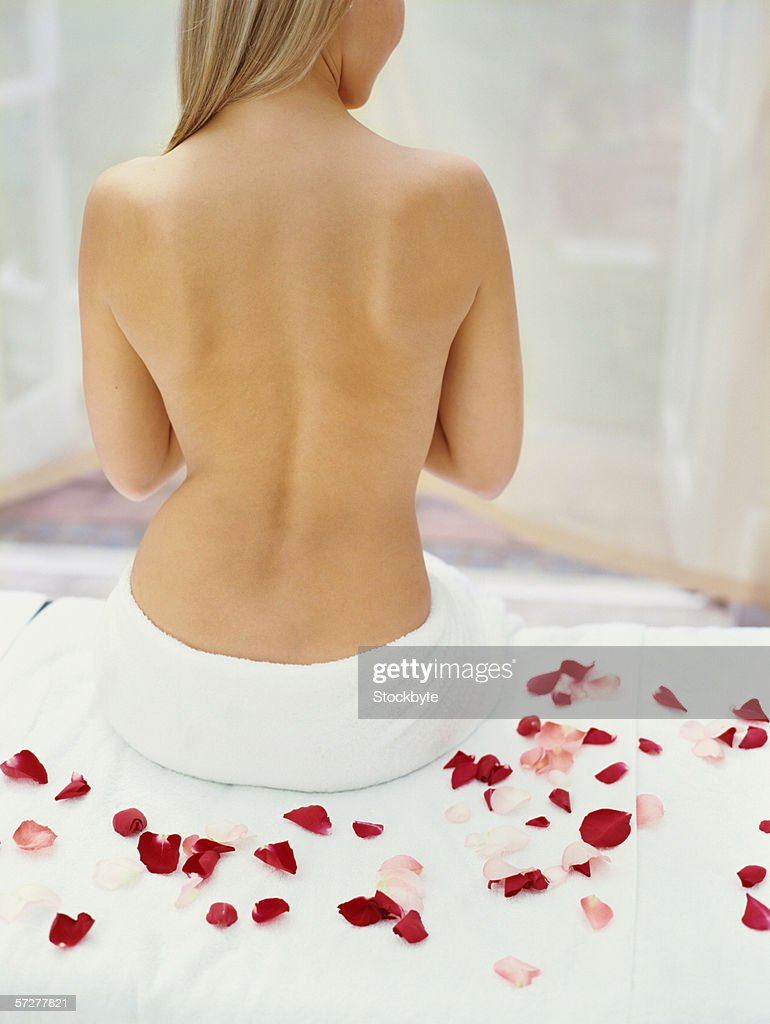 Rear view of a young woman sitting on a massage table with rose petals : Stock Photo