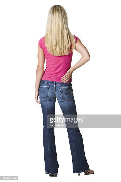 Rear view of a young woman standing with her hand on her hip
