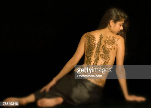 rear view of a young woman with a tattoo on her back stock foto getty images. Black Bedroom Furniture Sets. Home Design Ideas