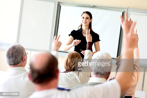 Rear View of Adult Students Raising Hands on Seminar
