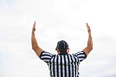 Rear view of American football judge shoving touchdown against the sky.