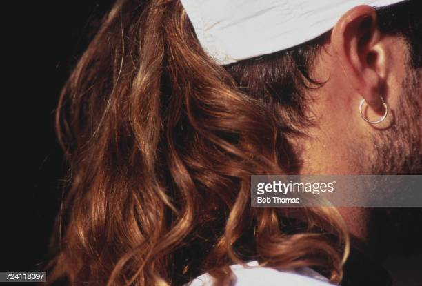 Rear view of American tennis player Andre Agassi's long hair emerging like a pony tail from his cap during competition to reach and win the final of...