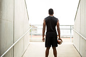 Silhouete of an African American teenager holding a football.