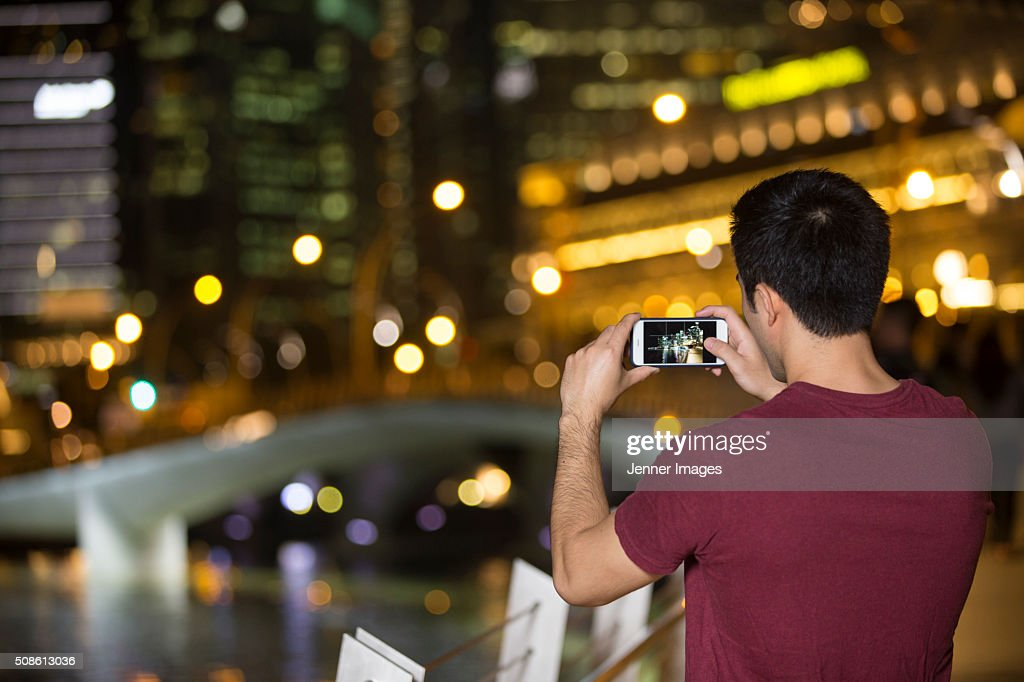 Rear view of an Asian man taking photo at night of city. : Stock Photo