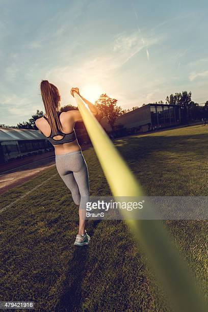 Rear view of an athletic woman with javelin.