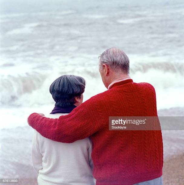Rear view of an elderly couple sitting at the beach with arms around each other
