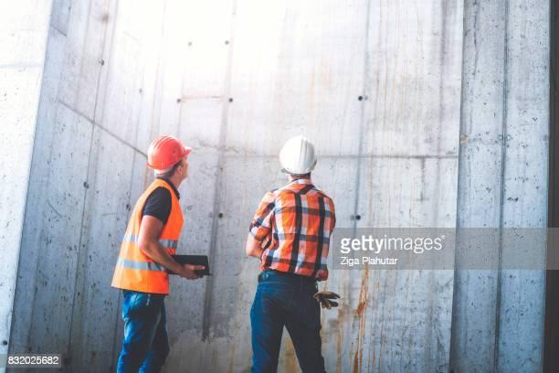 エンジニア、請負業者が工事現場の簡単な会議を持っていることの背面図