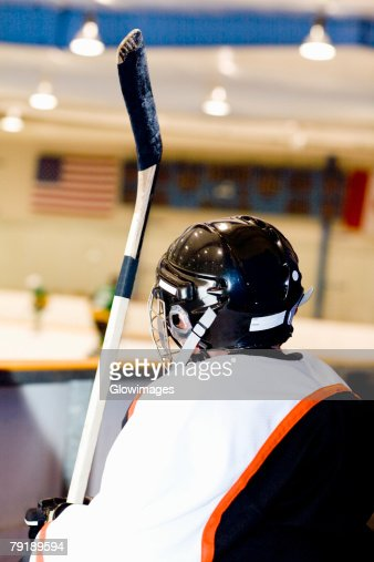 Rear view of an ice hockey player near an ice rink : Stock Photo