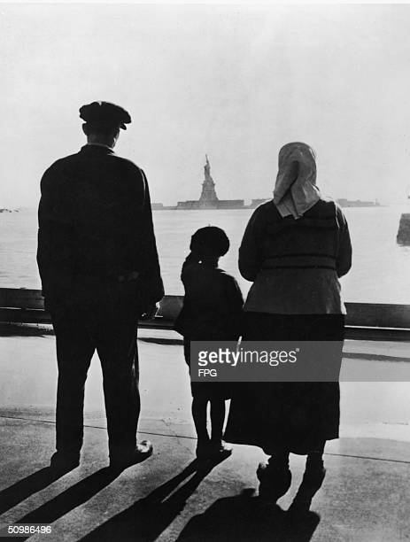 Rear view of an immigrant family on Ellis Island looking across New York Harbor at the Statue of Liberty 1930s
