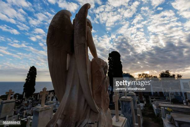 Rear view of angel sculpture on grave in cemetery
