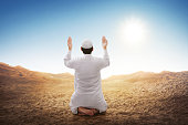Rear view of asian muslim man sitting and praying at desert background