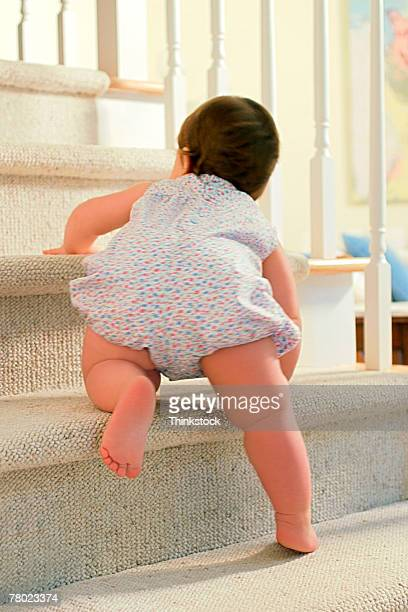 Rear view of baby girl climbing up stairs.