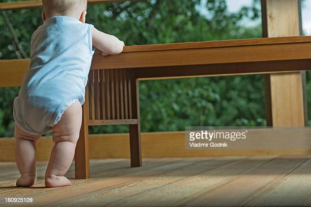 rear view of baby in living room standing at table