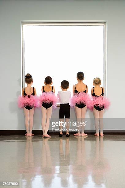 Rear view of ballet students standing by window
