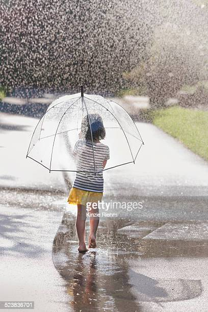 Rear view of barefoot girl carrying umbrella walking through street puddle