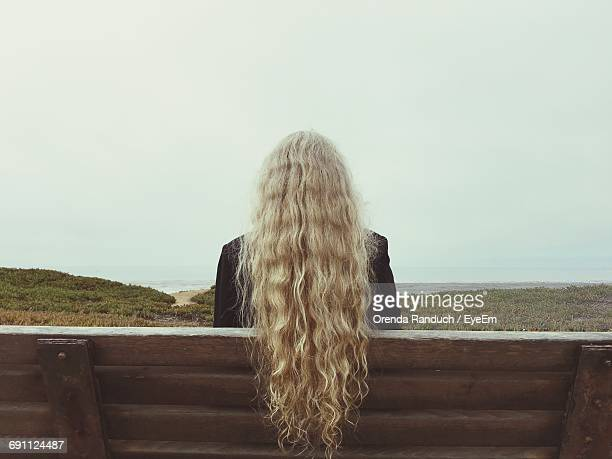 Rear View Of Blond Woman Sitting On Bench At Cliff Against Sky