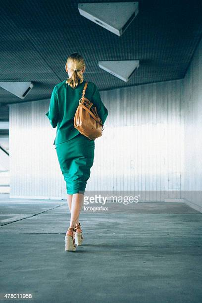rear view of blonde businesswoman walks through a tunnel