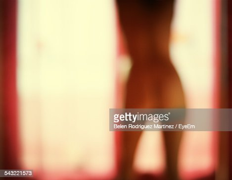 Rear View Of Blurred Sensuous Woman Standing By Window