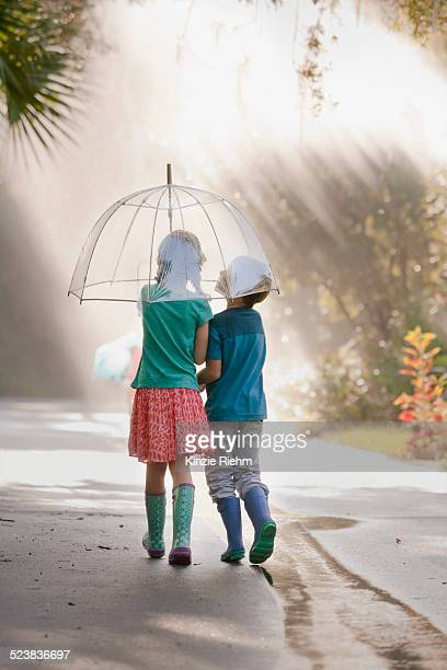 Rear view of boy and girl carrying umbrella on street