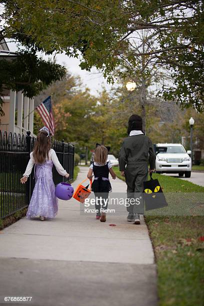 Rear view of boy and sisters trick or treating walking along sidewalk