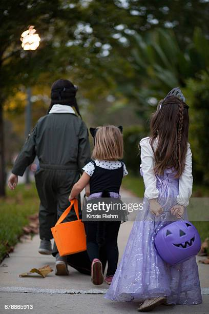 Rear view of boy and sisters trick or treating walking on sidewalk