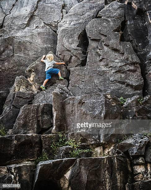 Rear view of boy climbing rock face