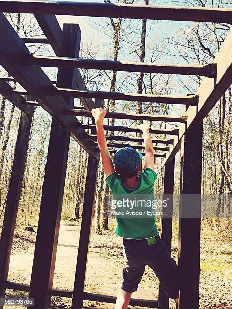 Rear View Of Boy Hanging On Monkey Bars In Park