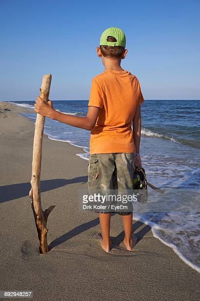 Rear View Of Boy Holding Stick And Standing On Shore Against Clear Sky