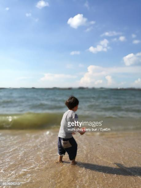 Rear View Of Boy In Sea Against Sky On Sunny Day