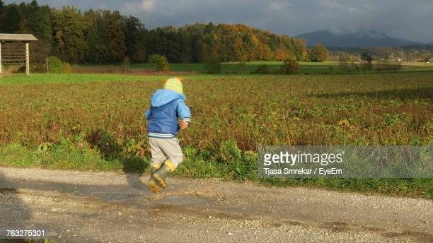 Rear View Of Boy Jumping On Puddle By Field