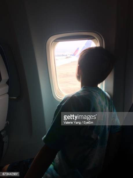 Rear View Of Boy Looking Out Of Airplane Window