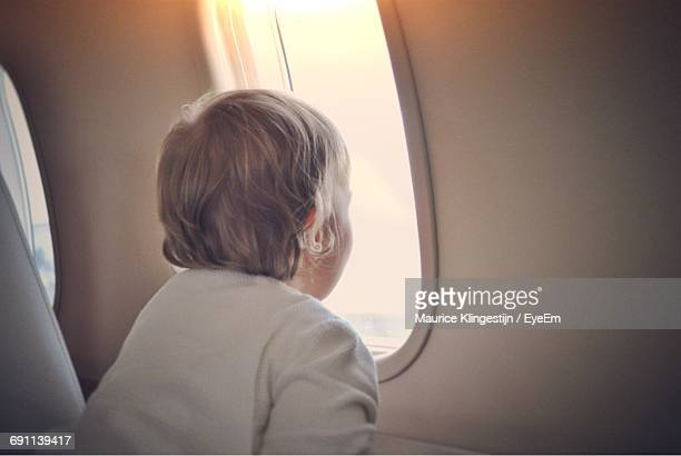 Rear View Of Boy Looking Through Airplane Window During Sunset