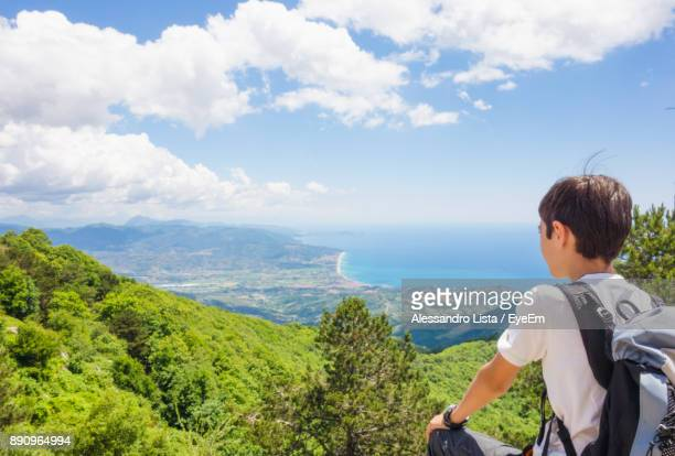 Rear View Of Boy On Mountain Against Cloudy Sky
