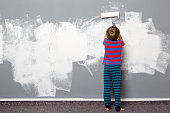 Rear view of boy painting wall