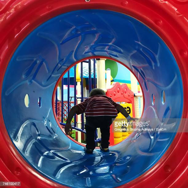 Rear View Of Boy Playing On Plastic Tunnel At Playground