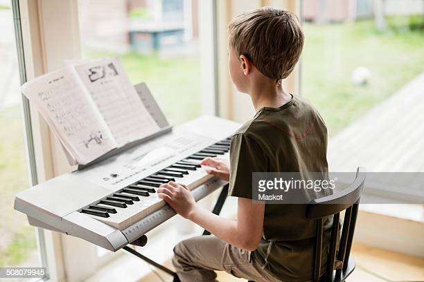 Rear view of boy playing piano at home