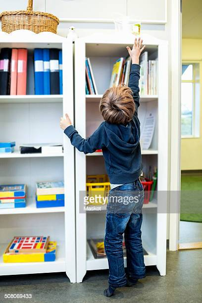 Rear view of boy reaching for container on shelf in kindergarten