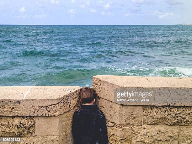 Rear View Of Boy Standing Amidst Retaining Wall Against Sea