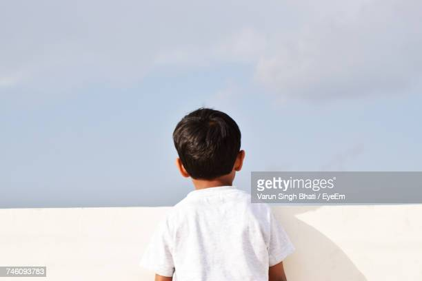 Rear View Of Boy Standing At Retaining Wall Against Sky