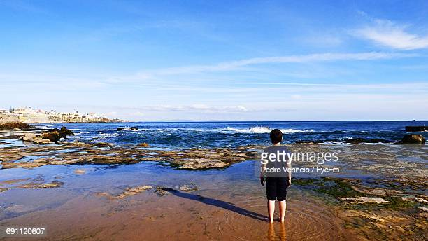 Rear View Of Boy Standing At Sea Shore Against Sky