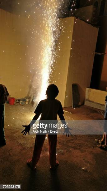 Rear View Of Boy Standing By Illuminated Firework Fountain At Night