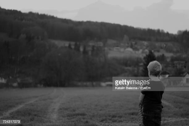 Rear View Of Boy Standing On Grassy Field Against Mountain