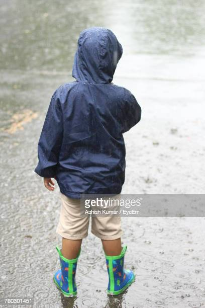Rear View Of Boy Standing On Puddle Collected On Road During Rainy Season