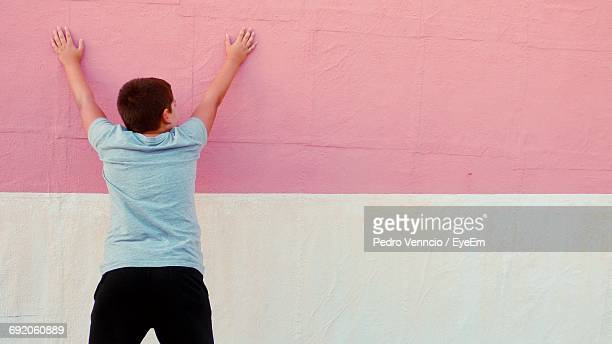 Rear View Of Boy Touching Wall