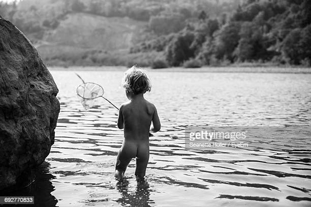 Rear View Of Boy With Fishing Net In Lake