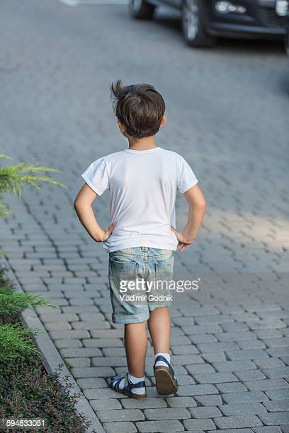 Rear view of boy with hands on hip standing on street