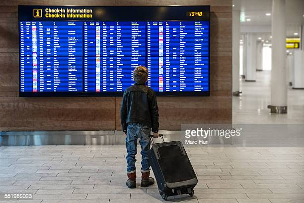 Rear view of boy with wheeled suitcase looking at airport departure board