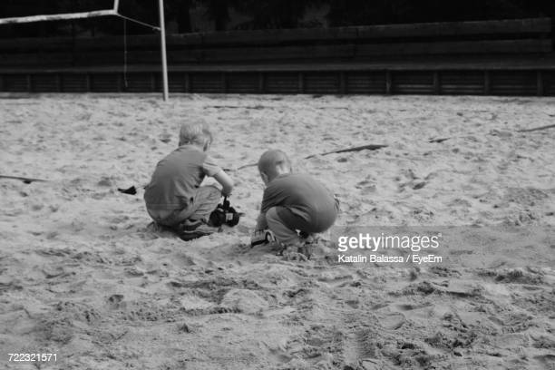 Rear View Of Boys Playing On Sand At Beach